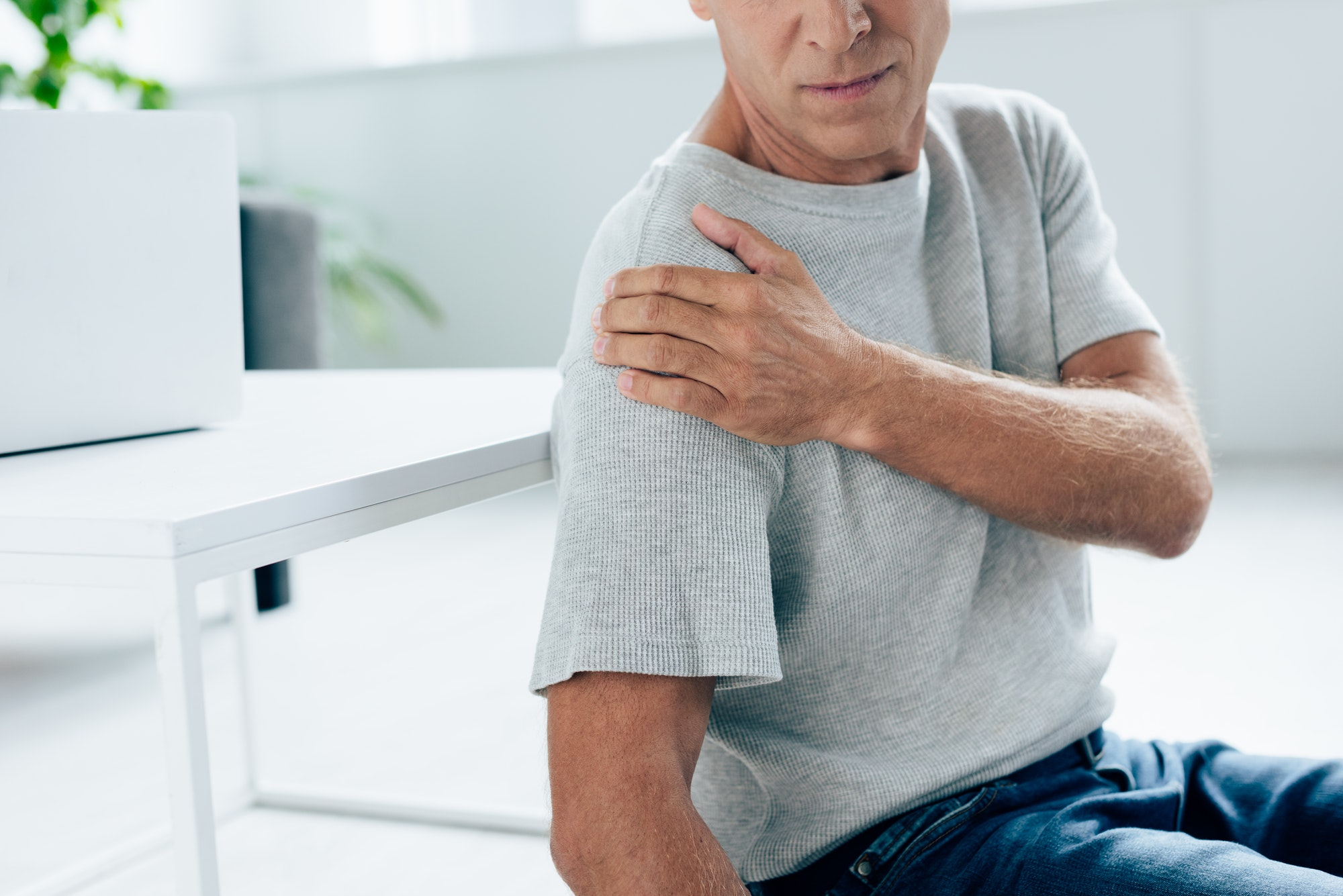 cropped view of man in t-shirt feeling pain in shoulder in apartment