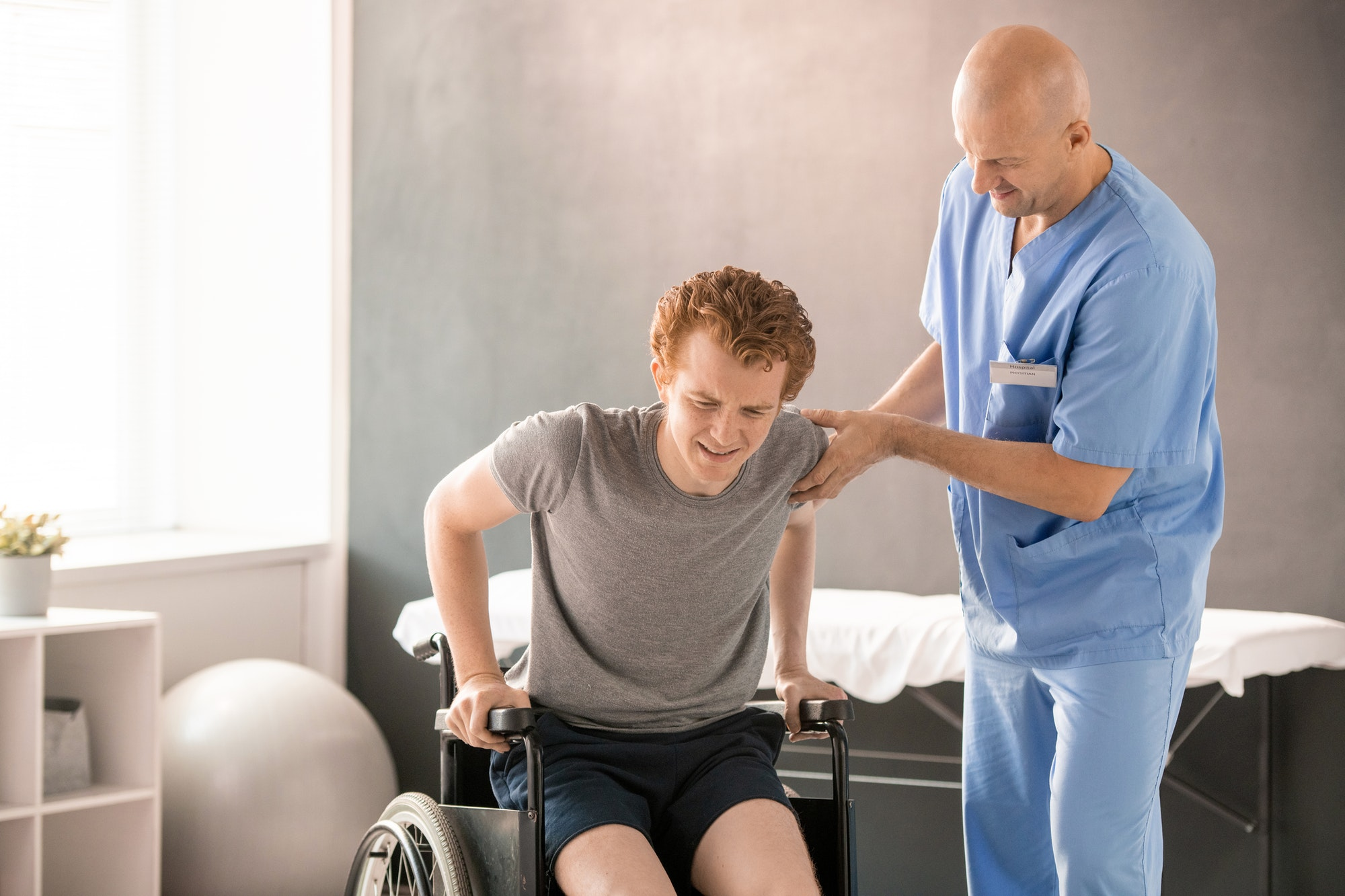 Mature clinician in uniform helping young man in pain to sit in wheelchair